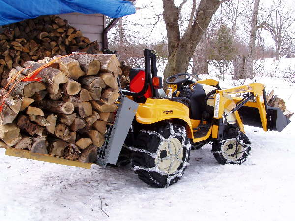Hauling firewood with my 6284D. Note chains on all four corners.